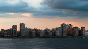 Modern residential building on the banks of the river at sunset. Timelapse stock video footage