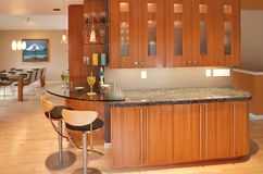 Modern Residential Home Interior. Modern kitchen cabinetry, glass bar with stools and dining table.  Mid-century modern design, with Asian accents Stock Image