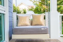 A modern resin swing in a porch with garden background. Brown pillows on modern resin hanging swing with chain in a porch with garden background Royalty Free Stock Photos