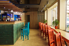 Modern restaurant, bar or cafe interior. Modern restaurant or cafe interior. Public place interior design, bright red and blue wooden chairs, large windows and royalty free stock photography