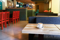 Modern restaurant, bar or cafe interior. Table with coffee cup in modern restaurant or cafe interior. Public place interior design, bright red wooden chairs and royalty free stock photos