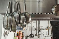 Modern restaurant kitchen interior with frying pans. Modern shiny kitchen with stainless steell kitchenware and equipment for restaurant cooking. Closeup of royalty free stock photo