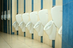 Modern restroom interior with urinal row Royalty Free Stock Images