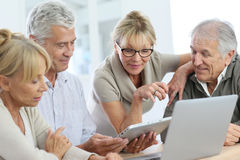 Modern retired people enjoying using electronical devices. Group of retired senior people using laptop and tablet Stock Images