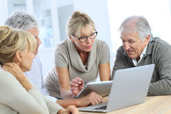 Modern retired people on tablet and laptop Stock Photo