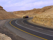 Modern road through the desert. A freshly paved road with white and yellow markings is winding through the barren  mountainous desert. A yellow truck makes it's Royalty Free Stock Photo