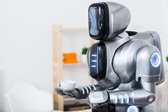 Modern robot holding cup of coffee Royalty Free Stock Photos