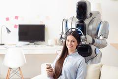 Modern robot wearing headphones on smiling girl Royalty Free Stock Photo