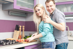 Modern romantic couple preparing meal at home. Portrait of a happy modern romantic couple preparing fresh breakfast. Woman is pregnant. Indoor shot stock photos