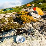 Modern rond kompas op een steen in de toendra dichtbij tent het kamperen Het concept reis en actieve levensstijl royalty-vrije stock foto