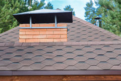 Modern roofing and decoration of chimneys. Flexible bitumen or slate shingles. The absence of corrosion and condensation due to the flexible roof Stock Photo
