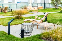 Modern rooftop patio with wooden armchair during the day stock images