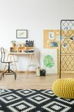 Modern room decor. With desk, pouf, carpet, posters and moodboard royalty free stock photo
