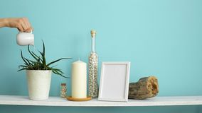 Modern room decoration with picture frame mockup. White shelf against pastel turquoise wall with candle and rocks in bottle. Hand stock footage