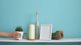 Modern room decoration with Picture frame mockup. White shelf against pastel turquoise wall with Candle and rocks in bottle. Hand. Putting down potted succulent stock video