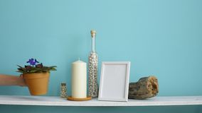 Modern room decoration with Picture frame mockup. White shelf against pastel turquoise wall with Candle and rocks in bottle. Hand. Putting down potted violet stock video footage
