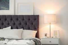 Modern room interior with comfortable bed and stylish lamp Royalty Free Stock Photos