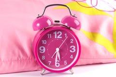 Modern rosa ringklocka på säng Arkivfoton