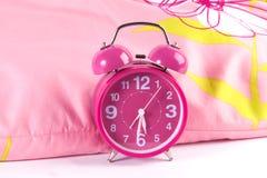 Modern rosa ringklocka på säng Arkivbilder