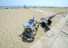 Modern rullstol vid havet i sommar med stora hjul Arkivfoto