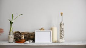 Modern rumgarnering med modellen för bildram Hyllan mot den vita väggen med den dekorativa stearinljuset, exponeringsglas och v