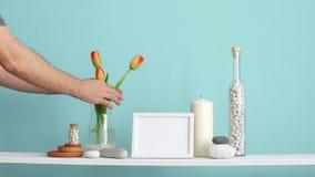 Modern rumgarnering med modellen f?r bildram Hyllan mot turkosv?ggen med den dekorativa stearinljuset, exponeringsglas och vaggar arkivfilmer