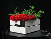 Modern rustic bouquet of red roses in wood box and green leafs o Royalty Free Stock Photography