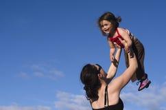Modern rymmer henne dottern upp i luften royaltyfri foto