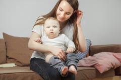 Modern rymmer på händer hennes favorit- barn som går att ändra honom kläder fotografering för bildbyråer