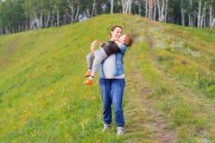 Modern rymmer sonen i henne armar Arkivfoton