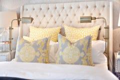 Modern sängcloseup med kuddar och lampor på lyxiga hus royaltyfri fotografi