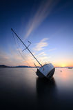 Modern sailing yacht stranded on a beach at sunset Royalty Free Stock Photo