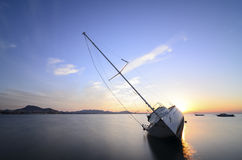 Modern sailing yacht stranded on a beach at sunset Stock Photo