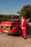 Modern Santa Claus. Santa fills his car up in preparation to delivery Royalty Free Stock Images
