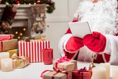 Modern Santa Claus using gadget. Close up of Father Frost hands in red gloves holding digital tablet. Present boxes on desk Stock Photos