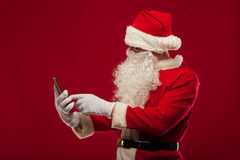 Modern Santa Claus using tablet pc over red background. Christma Royalty Free Stock Photos