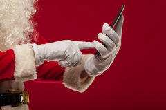 Modern Santa Claus using tablet pc over red background. Christma Stock Photo