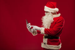 Modern Santa Claus using tablet pc over red background. Christma Stock Photography