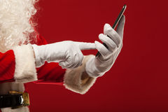 Modern Santa Claus using tablet pc over red Stock Images