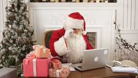 Modern Santa Claus working on his laptop and preparing presents. Professional shot on Lumix GH4 in 4K resolution. You can use it e.g. in your commercial video Royalty Free Stock Photo