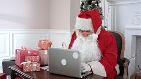 Modern Santa Claus working on his laptop and preparing presents. Timelapse shot. Professional shot on BMCC RAW with high dynamic range. You can use it e.g. in Stock Photo