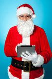 Modern Santa using digital touch screen device Royalty Free Stock Photo