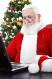 Modern Santa using laptop Stock Photography