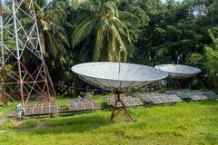 Modern satellite dish. And solar panels in the jungle forest. satellite dish, satellite antenna, satellite receiver royalty free stock photos