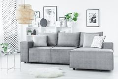 Modern scandi living room interior. Silver table next to a grey corner settee in modern, scandi living room interior with gallery on the wall Royalty Free Stock Photo