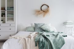 Modern scandinavian sunny bedroom with bed and pillows. Space with white walls and eco decor. A bed royalty free stock photos