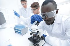 Modern scientist uses a microscope in a laboratory. Science and health stock photo