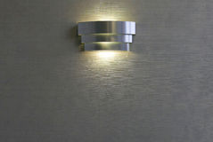 Modern Sconce Light Fixture. Silver modern sconce lighting fixture mounted on wall Royalty Free Stock Photos