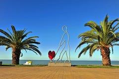 Modern sculpture with a heart on the beach Stock Photos