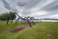 Modern sculpture in park overlooking city downton Royalty Free Stock Images